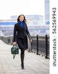 Small photo of beautiful smiling businesswoman quick step moves along the promenade along the river in a big city. fashion