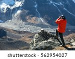 mountain climber in warm and... | Shutterstock . vector #562954027
