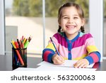 little girl is drawing picture | Shutterstock . vector #563200063