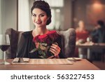 Stock photo elegant brunette lady with bouquet of red roses in restaurant 563227453