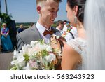 bride wearing buttonhole on a... | Shutterstock . vector #563243923
