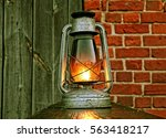 Small photo of A metal lit lantern with yellow amber light emenating throught glass placed outdoors next to an old dark plank wood fence and a red brick wall.