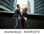 couple jumping near skyscrapers | Shutterstock . vector #563592373