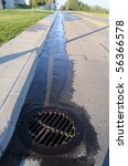 Water Pouring into Street Storm Drain - stock photo