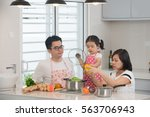 asian family cooking at kitchen   Shutterstock . vector #563706943
