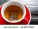 red ceramic cup of tea served... | Shutterstock . vector #563873983