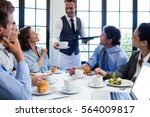 waiter serving coffee to the... | Shutterstock . vector #564009817