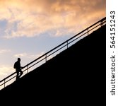 Small photo of Silhouette of Man climbing the way or steps over sunset sky background. Concept of road of success, ambition, aim and goal.