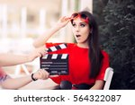 Small photo of Surprised Actress with Oversized Sunglasses Shooting Movie Scene - Diva in red dress and big shades starring in an artistic film