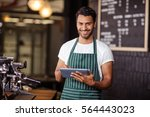 smiling barista using tablet... | Shutterstock . vector #564443023