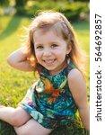 charming girl sitting on green... | Shutterstock . vector #564692857