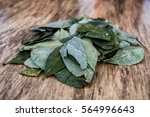 Small photo of Batch of coca leaves on wooden table. Used in countries like Peru and Bolivia to combat altitude sickness.
