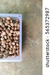 Small photo of Dried Betel Nut or Areca Nut in plastic basket on rough cement ground.