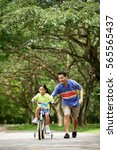 Small photo of Girl cycling, father running alongside her