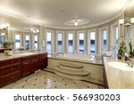 Small photo of Luxurious master bathroom interior boasts jetted tub with curved windows facing the lake, two cherrywood vanity cabinets facing each other and glossy marble floor. Northwest, USA
