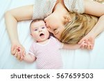 mother kisses baby lying on the ... | Shutterstock . vector #567659503