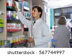 Small photo of Portrait of two amiable pharmacists working in modern farmacy