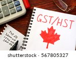 Small photo of GST / HST written in a note on a wooden surface.
