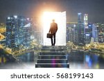 Small photo of Pathway of opportunity. Back view of businessman exiting abstract night city room with stairs to enter open door with bright light. Success concept