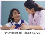 teacher and student smile at... | Shutterstock . vector #568546723