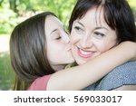 Small photo of teenage girl makes a big kiss and a hug to her adored mother