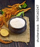 Small photo of Flour amaranth in a clay cup, a spoon with grain, brown flower with leaves on a napkin from a sacking on a background of wooden boards
