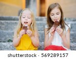two cute little sisters eating... | Shutterstock . vector #569289157