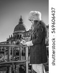 Small photo of Another world vacation. Portrait of elegant fashion-monger in fur hat on embankment in Venice, Italy looking on Venetian mask