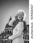 Small photo of Another world vacation. Portrait of elegant fashion-monger in fur hat in Venice, Italy wearing Venetian mask