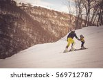 Small photo of TSAGHKADZOR, ARMENIA - FEBRUARY 5, 2015: An undefined male teaches a child to ski. Freedom, extreme, sport, free ride, happiness, teach, teaching concepts. Toned with old fashioned sepia colors.