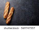 sliced bread over dark stone... | Shutterstock . vector #569747557