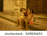 Small photo of HAVANA, CUBA - APRIL 06, 2014: Latin American and Afro-American little girls are smiling and sitting on steps on a porch near the house under a streetlight at night at downtown