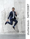 jumping for joy man in blue suit | Shutterstock . vector #569923087