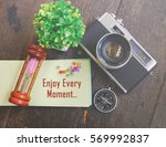 Small photo of word ENJOY EVERY MOMENT on note pad with decorative item and wooden background for weekend enjoyment concept