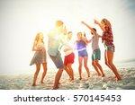 friends dancing at beach on... | Shutterstock . vector #570145453