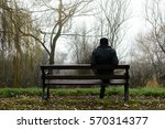 Man Sits On A Bench In The Par...