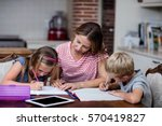 Small photo of Mother helping kids with their homework at home