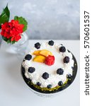 Small photo of ?ake with cream, pistachios and berries and fruits on white table with grey background and vase with flowers