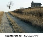 Road through prairie to old school. - stock photo