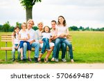 big family sitting on a bench | Shutterstock . vector #570669487