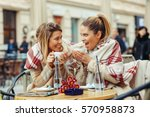 Two Young Women In A Cafe Have...