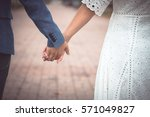 couple holding hands in park... | Shutterstock . vector #571049827