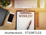 Notepad with a paper written WISHLIST on wooden office desk with flare effect