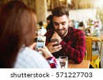 couple in cafe using their... | Shutterstock . vector #571227703