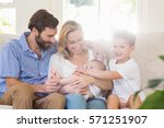 parents sitting on sofa with... | Shutterstock . vector #571251907