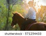 young pretty girl riding a horse | Shutterstock . vector #571254433
