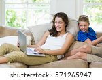 mother and son sitting on sofa... | Shutterstock . vector #571265947