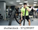 man with battle ropes exercise... | Shutterstock . vector #571299397