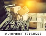 Small photo of Small paper cartons or boxes in shopping cart with one falls outside on a laptop keyboard. Concept about online shopping that everybody can buy or purchase everything easily at hand just a few clicks.