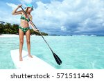 young woman paddling on sup... | Shutterstock . vector #571511443